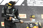 Second placed Mercedes driver Lewis Hamilton of Britain sprays sparkling wine on winner Red Bull driver Max Verstappen of the Netherlands, after the Emilia Romagna Formula One Grand Prix, at the Imola racetrack, Italy, Sunday, April 18, 2021. (AP Photo/Luca Bruno)