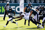 Philadelphia Eagles' Miles Sanders (26) runs past Baltimore Ravens' Calais Campbell (93) during the first half of an NFL football game, Sunday, Oct. 18, 2020, in Philadelphia. (AP Photo/Chris Szagola)