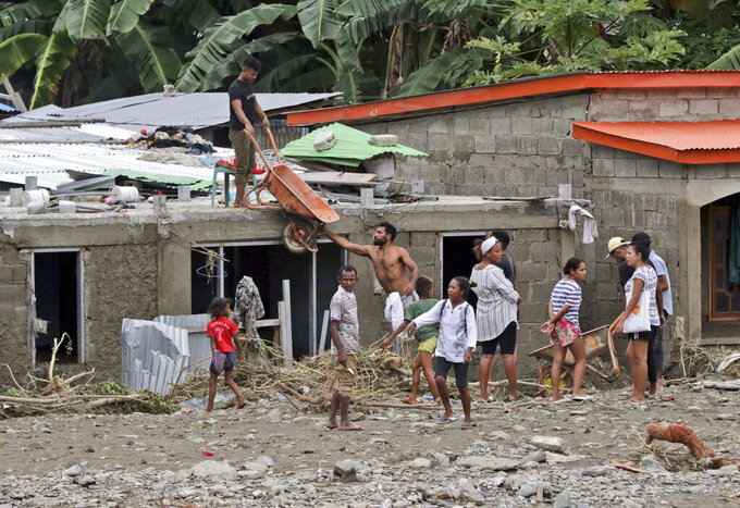 Residents clear up debris from around their houses following a flood in Dili, East Timor, Monday, April 5, 2021. Multiple disasters caused by torrential rains in eastern Indonesia and neighboring East Timor have left a number of people dead or missing as rescuers were hampered by damaged bridges and roads and a lack of heavy equipment Monday. (AP Photo/Kandhi Barnez)