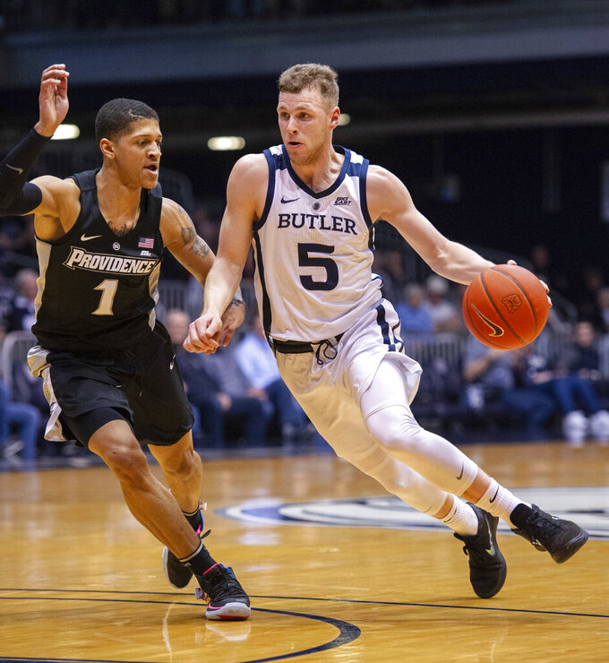 Butler guard Paul Jorgensen (5) drives the ball around the defense of Providence guard Makai Ashton-Langford (1) during the first half of an NCAA college basketball game, Tuesday, Feb. 26, 2019, in Indianapolis. (AP Photo/Doug McSchooler)