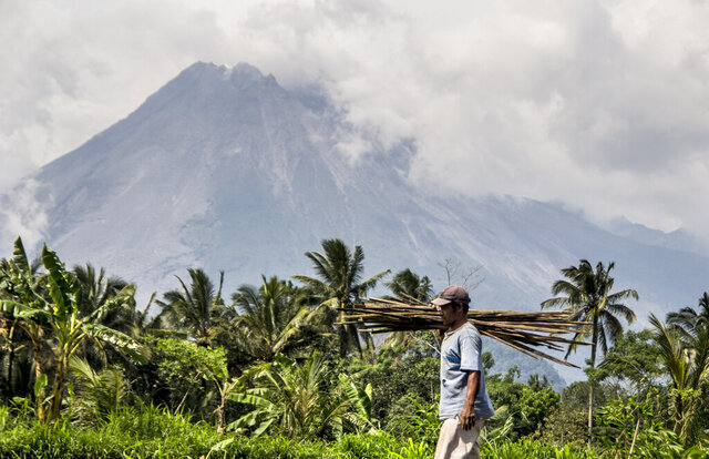 A farmer walks on his field as Mount Merapi is seen in the background in Sleman, Indonesia, Thursday, Nov. 5, 2020. Indonesian authorities raised the danger level for the volatile Mount Merapi volcano on the densely populated island of Java on Thursday and ordered a halt to tourism and mining activities. (AP Photo/Slamet Riyadi)