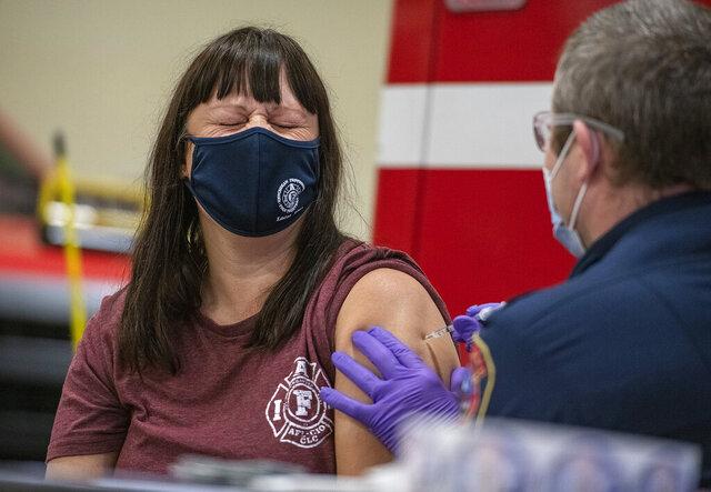 Fire Marshal Gretchen O'Sullivan receives a COVID-19 vaccine shot from Senior Paramedic Greg Karlik on Saturday, Dec. 19, 2020 at Fire Station 1 in Ketchikan, Alaska. (Dustin Safranek/Ketchikan Daily News via AP)