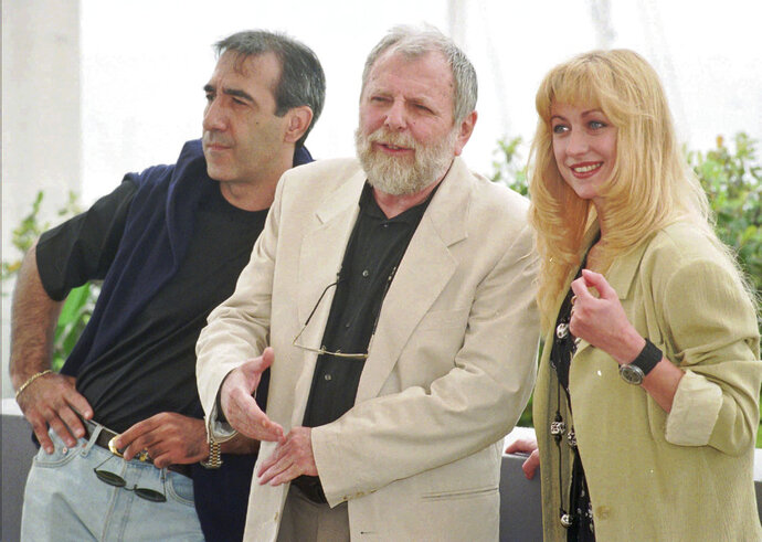 FILE- In this May 15, 1996 file photo, Romanian director Lucian Pintilie, center, poses with actors Razvan Vasilescu, left, and Cecilia Barbora before the presentation of his movie
