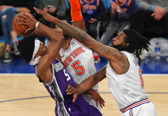 Sacramento Kings guard De'Aaron Fox (5) puts up a shot against New York Knicks center DeAndre Jordan (6) and guard Dennis Smith Jr. (5) during the third quarter of an NBA basketball game, Saturday, March 9, 2019, in New York. The Kings won 102-94. (AP Photo/Julie Jacobson)