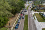 FILE - In this Thursday, March 19, 2020 file photo, drivers form a long line for free drive-through COVID-19 coronavirus testing at a medical center in north Houston, Texas. (Mark Mulligan/Houston Chronicle via AP)