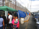 FILE - In this May 5, 2019, file photo, migrants walk between tents, left, and cars waiting to cross the border in San Luis Rio Colorado, Mexico, and Arizona. Newly unsealed court documents show that many U.S. holding cells along the Mexican border were less than half-full, or even empty, during an unprecedented surge of asylum-seeking Central American families. The documents cast doubt on the Trump administration's claims that people had to wait in Mexico because there weren't enough resources to accommodate them. (AP Photo/Elliot Spagat, File)