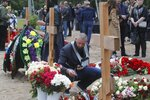 A man puts a candle at the grave of Captain 3rd rank Vladimir Sukhinichev, one of the 14 crew members who died in a fire on a Russian navy's deep-sea research submersible, at the Serafimovskoye memorial cemetery during a funeral ceremony in St. Petersburg, Russia, Saturday, July 6, 2019. Russian President Vladimir Putin has awarded the nation's highest honors to 14 seamen who died in a fire on one of the navy's research submersibles. (AP Photo/Dmitri Lovetsky)