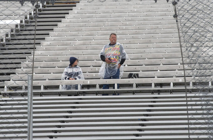 NASCAR fans wait to see if the rain will stop for the start of a NASCAR Cup series auto race Sunday, May 5, 2019, at Dover International Speedway in Dover, Del. (AP Photo/Jason Minto)