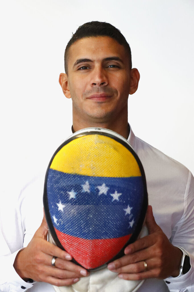 FILE - In this Nov. 4, 2019, file photo, Venezuelan fencing champion Ruben Limardo poses for a photo while holding his fencing mask with the Venezuelan flag pained on the front during an interview in Miami. Limardo, who won the Olympic gold in London 2012, is currently delivering food for an online platform in Poland because of the ongoing coronavirus pandemic. (AP Photo/Wilfredo Lee)