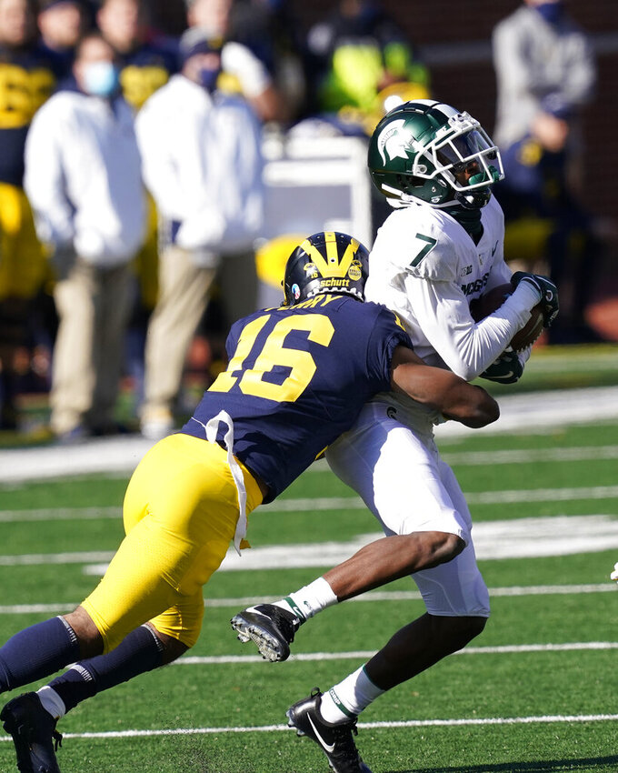 Michigan State wide receiver Ricky White (7) is tackled by Michigan defensive back Jalen Perry (16) during the second half of an NCAA college football game, Saturday, Oct. 31, 2020, in Ann Arbor, Mich. (AP Photo/Carlos Osorio)