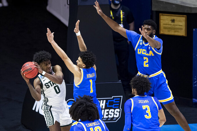 Michigan State's Aaron Henry (0) is defended by UCLA's Jules Bernard (1), Tyger Campbell (10), Johnny Juzang (3) and Cody Riley (2) during the second half of a First Four game in the NCAA men's college basketball tournament, early Friday, March 19, 2021, at Mackey Arena in West Lafayette, Ind. UCLA won 86-80. (AP Photo/Robert Franklin)
