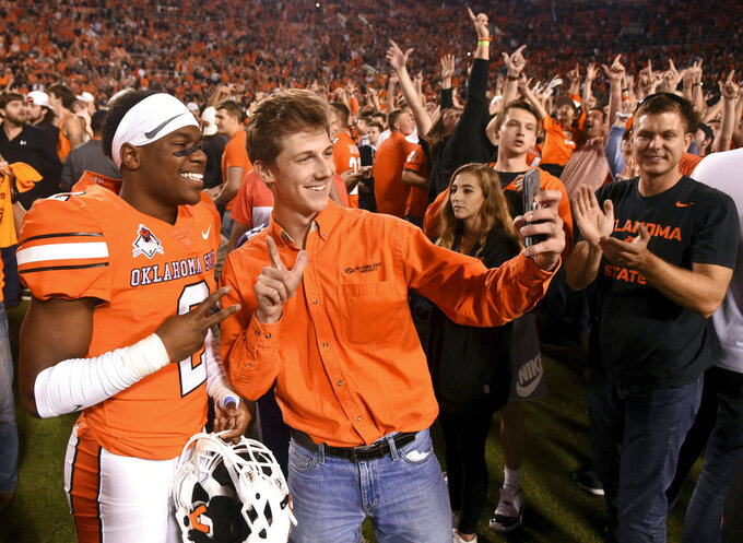 Oklahoma State wide receiver Tylan Wallace takes a photo with fans following an NCAA college football game in Stillwater, Okla., Saturday, Oct. 27, 2018. Wallace had two touchdowns in Oklahoma State's 38-35 win over Texas. (AP Photo/Brody Schmidt)