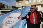 In this Monday, Oct. 14, 2019 photo, Abbas Gulenc, 60, a council member of Turkey's President Recep Tayyip Erdogan's Justice and Development party (AKP) gathers with others in a show of support for Turkey's operation in Syria, beside a poster of Erdogan, in the border town of Akcakale, Sanliurfa province, southeastern Turkey. Since Turkey announced its incursion into neighbouring Syria to clear out Kurdish fighters last week, patriotic sentiment has run high. (AP Photo/Lefteris Pitarakis, FILE)