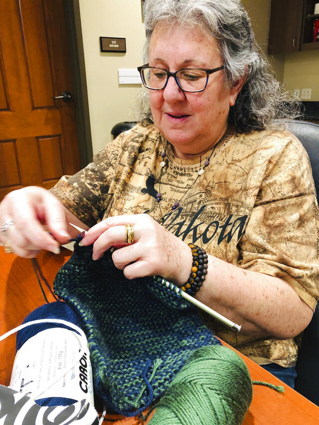 In this Monday, Dec. 30, 2019 photo, Robin Carmody knits at the at the Deadwood Chamber of Commerce in Deadwood, S.D. Carmody generally uses 13 and 15 sized knitting needles, worsted yarn, and knits with two yarns together to craft her creations. (Robin Carmody/Black Hills Pioneer via AP)
