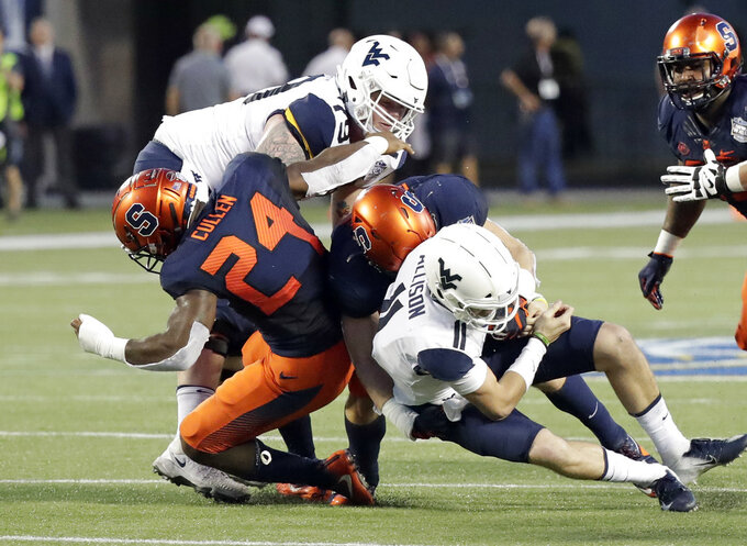 West Virginia quarterback Jack Allison (11) is sacked by Syracuse linebacker Shyheim Cullen (24) and a teammate during the first half of the Camping World Bowl NCAA college football game Friday, Dec. 28, 2018, in Orlando, Fla. (AP Photo/John Raoux)