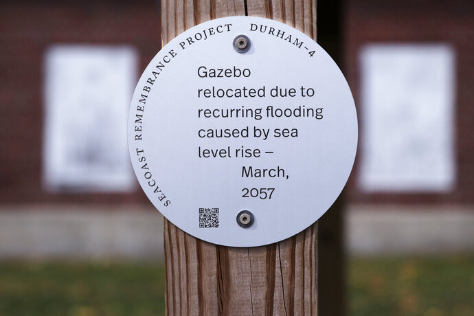 A sign, part of a public design installation by artist Thomas Starr, is displayed on a gazebo outside the University of New Hampshire boathouse in Durham, N.H., Wednesday, Oct. 16, 2019. Starr, a graphic and information design professor from Boston's Northeastern University, created the project to address possible effects of climate change. (AP Photo/Charles Krupa)