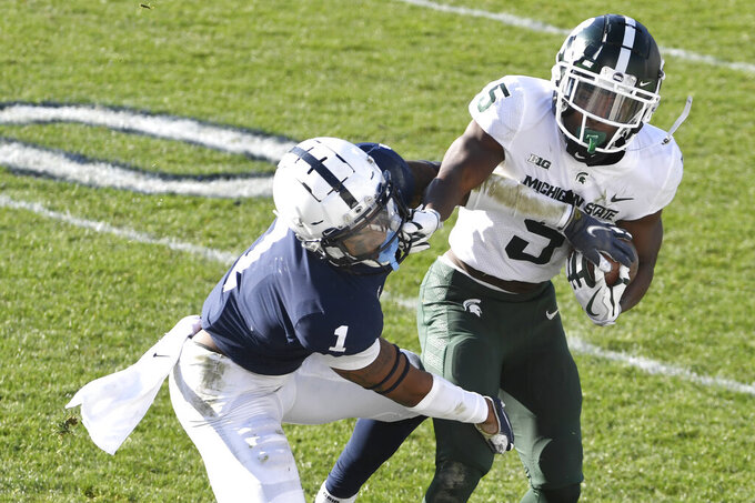 Michigan State wide receiver Jayden Reed (5) fights off a tackle attempt by Penn State safety Jaquan Brisker (1) in the second quarter of an NCAA college football game in State College, Pa., on Saturday, Dec. 12, 2020. Penn State defeated Michigan State 39-24. (AP Photo/Barry Reeger)