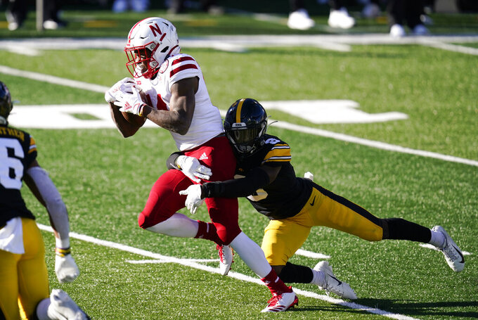 Nebraska running back Rahmir Johnson, left, breaks a tackle by Iowa defensive back Matt Hankins (8) during a 12-yard touchdown run in the second half of an NCAA college football game, Friday, Nov. 27, 2020, in Iowa City, Iowa. Iowa won 26-20. (AP Photo/Charlie Neibergall)