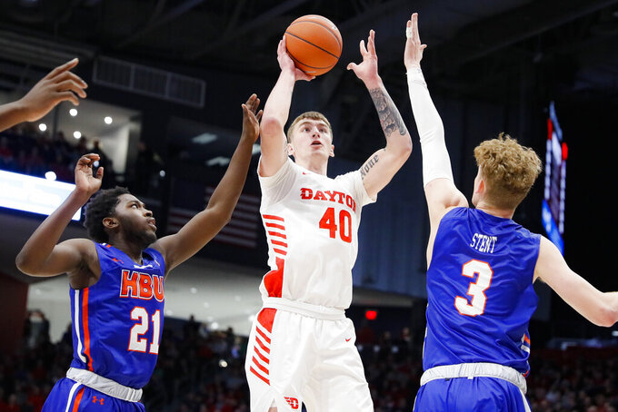 Dayton's Chase Johnson (40) shoots against Houston Baptist's Jackson Stent (3) and Noah Thomasson (21) during the second half of an NCAA college basketball game, Tuesday, Dec. 3, 2019, in Dayton, Ohio. (AP Photo/John Minchillo)