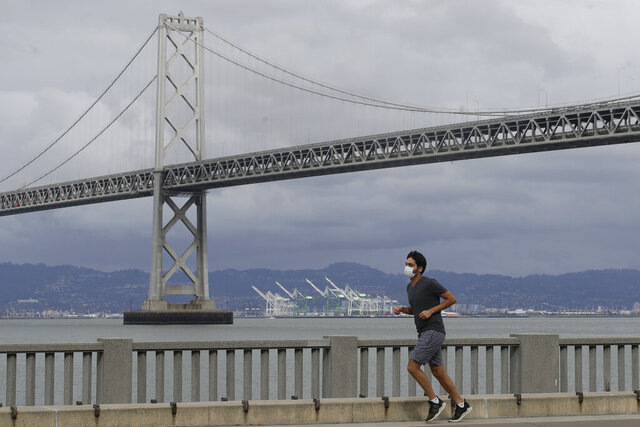 A man wears a mask to protect himself from the coronavirus while running in front of the San Francisco-Oakland Bay Bridge along the Embarcadero in San Francisco, Sunday, April 5, 2020. (AP Photo/Jeff Chiu)