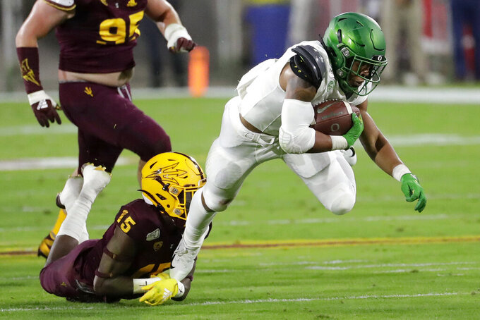 FILE - In this Nov. 23, 2019, file photo, Oregon running back CJ Verdell, right, is tackled by Arizona State safety Cam Phillips (15) during the first half of an NCAA college football game in Tempe, Ariz. The Ducks will have to replace five starters on the offensive line. But Oregon returns significant skill position players, including running back CJ Verdell. (AP Photo/Matt York, File)