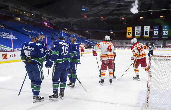 Vancouver Canucks' Nils Hoglander (36), of Sweden, celebrates his goal with Matthew Highmore (15), Jack Rathbone (3) and Tyler Myers (57) as Calgary Flames' Rasmus Andersson (4), of Sweden, and Nikita Nesterov (89), of Russia, skate to the bench during first period of an NHL hockey game in Vancouver, British Columbia, on Tuesday, May 18, 2021. (Darryl Dyck/The Canadian Press via AP)
