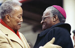 FILE - In this Monday, Jan. 1, 1990, file photo, Mayor David Dinkins, left, gets a hug from South African Bishop Desmond Tutu after Dinkins was sworn-in as New York City's first Black mayor, at inaugural ceremonies at City Hall in New York. Dinkins, New York City's first African-American mayor, died Monday, Nov. 23, 2020. He was 93. (AP Photo/Frankie Ziths, File)