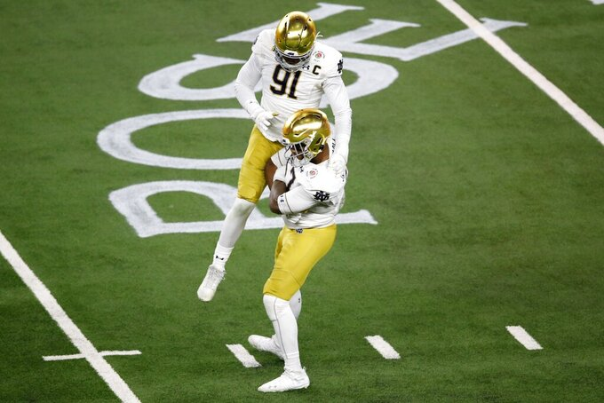 Notre Dame defensive lineman Jayson Ademilola, bottom, and defensive lineman Adetokunbo Ogundeji (91) celebrate after Ademilola knocked down a pass attempt by Alabama quarterback Mac Jones in the second half of the Rose Bowl NCAA college football game in Arlington, Texas, Friday, Jan. 1, 2021. (AP Photo/Roger Steinman)