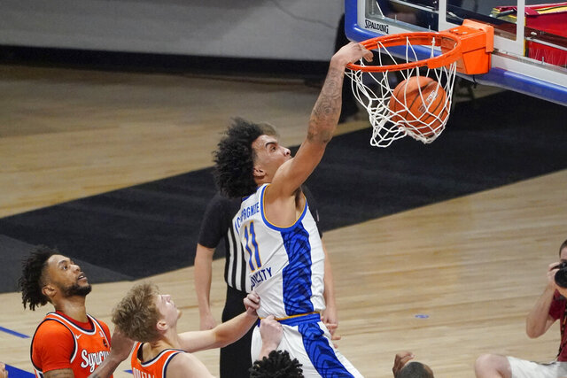 Pittsburgh's Justin Champagnie (11) dunks after getting by Syracuse's Alan Griffin, left, and Marek Dolezaj, center, during the second half of an NCAA college basketball game, Saturday, Jan. 16, 2021, in Pittsburgh. (AP Photo/Keith Srakocic)