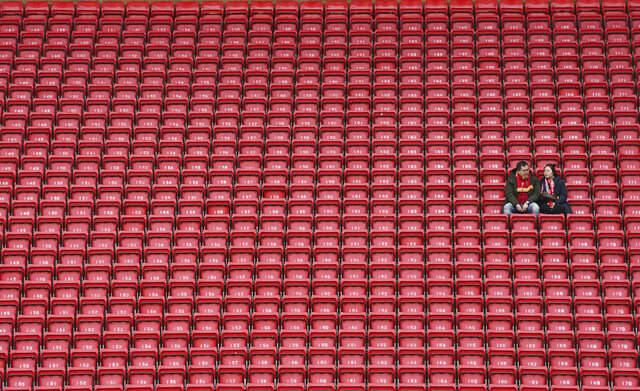 FILE - In this March 7, 2020, file photo, people sit surrounded by empty seats as they wait for the start of the English Premier League soccer match between Liverpool and Bournemouth at Anfield stadium in Liverpool, England. The crippling grip the coronavirus pandemic has had on the sports world has forced universities, leagues and franchises to evaluate how they might someday welcome back fans. (AP Photo/Jon Super, File)
