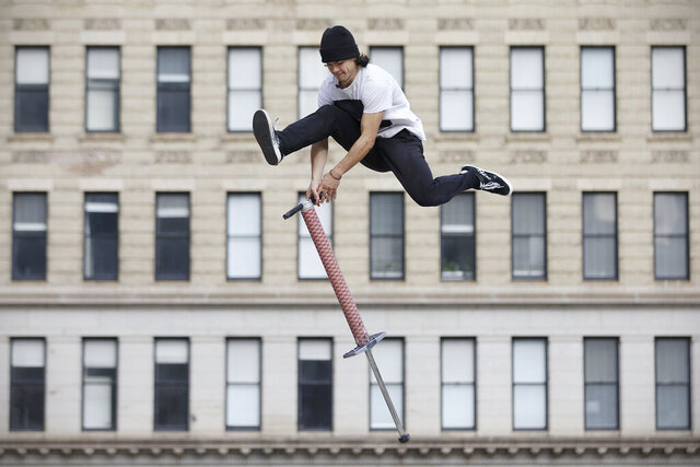 Nicolas Patino, an extreme pogo competitor, demonstrates a trick at Thomas Paine Plaza in Center City Philadelphia on Thursday, Dec. 3, 2020. (Tim Tai/The Philadelphia Inquirer via AP)