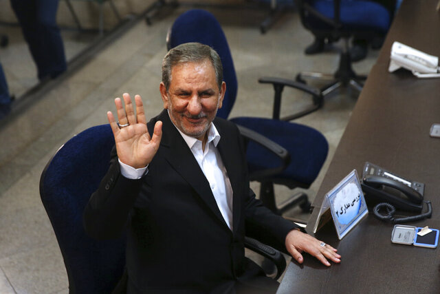 CORRECTS FIRST NAME TO ESHAQ: FILE - In this April 15, 2017 file photo, Iranian Vice-President Eshaq Jahangiri waves to media while registering his candidacy for the May 19, 2017, presidential elections, at the Interior Ministry, in Tehran, Iran. Jahangiri and two other Cabinet members have contracted the new coronavirus, semiofficial Fars News Agency reported Wednesday, March 11, 2020. The vast majority of people recover from the new virus. (AP Photo/Vahid Salemi, File)