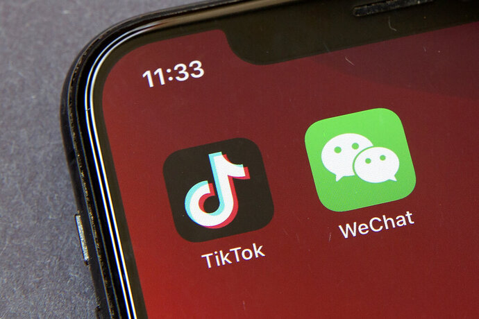 FILE - Icons for the smartphone apps TikTok and WeChat are seen on a smartphone screen in Beijing, in a Friday, Aug. 7, 2020 file photo.  Some U.S.-based users of WeChat are suing President Donald Trump in a bid to block an executive order that they say would effectively prohibit U.S. access to the popular Chinese messaging app. The complaint was filed Friday, Aug. 21, 2020 in San Francisco and asks a federal court judge to stop Trump's order from being enforced. It claims a ban would violate U.S. users' constitutional rights.  (AP Photo/Mark Schiefelbein, File)