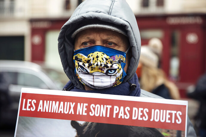 An advocates of animal rights holds a poster reading in French