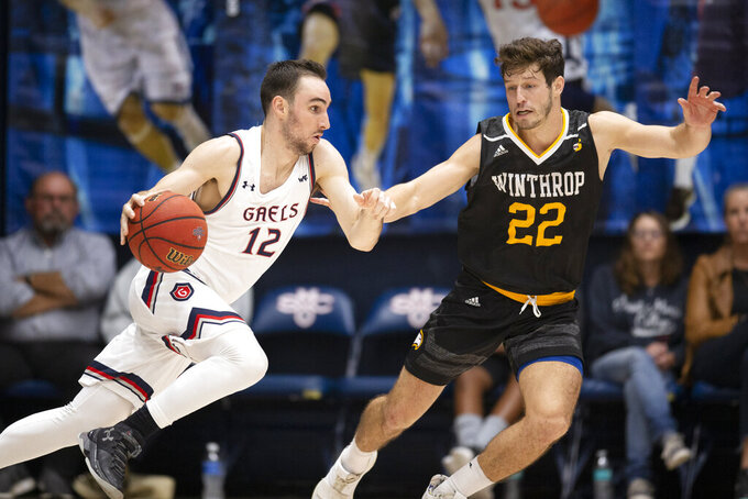 Saint Mary's guard Tommy Kuhse (12) drives past Winthrop guard Kyle Zunic (22) during the second half of an NCAA college basketball game, Monday, Nov. 11, 2019 in Moraga, Calif. Winthrop upset 18th-ranked Saint Mary's 61-59. (AP Photo/D. Ross Cameron)