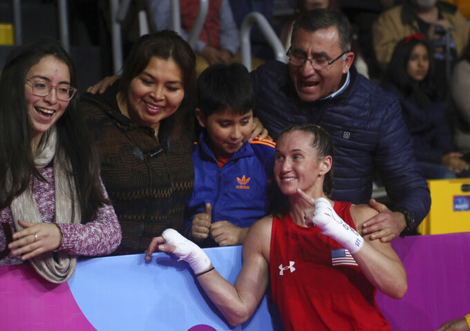 FILE - Virginia Fuchs of the United States poses with fans after her fight against Irismar Cardozo of Venezuela in the women's fly, 51 kg, boxing semifinal match at the Pan American Games in Lima, Peru,  in this Tuesday, July 30, 2019, file photo. Fuchs' obsessive-compulsive disorder sometimes compels her to use a dozen toothbrushes a night and to buy hundreds of dollars of cleaning products per week. Yet Fuchs is headed to Tokyo next week to compete in the Olympic boxing tournament, where she realizes it's almost impossible to avoid touching the blood, sweat and spit of her opponents.(AP Photo/Fernando Llano, File)