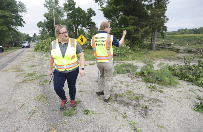 National Weather Service meteorologists Jaclyn Anderson, left and Kevin Wagner survey the damage to determine if there was a tornado in the Town of Concord, Wis., on Thursday, July 29, 2021. A line of thunderstorms arrived early Thursday generating numerous tornado warnings as well as high winds and near-constant lightning. (Mike De Sisti/Milwaukee Journal-Sentinel via AP)