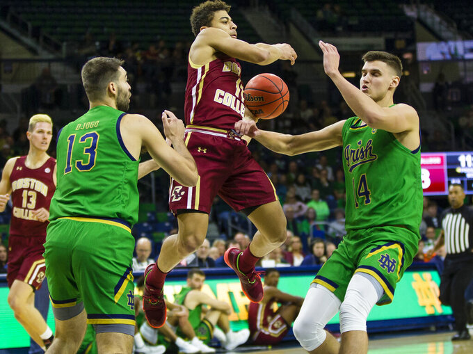 Boston College's Derryck Thornton (11) dishes out a pass defended by Notre Dame's Nikola Djogo (13) and Nate Laszewski (14) during an NCAA college basketball game Saturday, Dec. 7, 2019 at Purcell Pavilion in South Bend, Ind. (Michael Caterina/South Bend Tribune via AP)