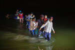 """In this March 24, 2021 photo, migrant families, mostly from Central American countries, wade through shallow waters after being delivered by smugglers on small inflatable rafts on U.S. soil in Roma, Texas.  The Biden administration said Monday that four families that were separated at the Mexico border during Donald Trump's presidency will be reunited in the United States this week in what Homeland Security Secretary Alejandro Mayorkas calls """"just the beginning"""" of a broader effort.   (AP Photo/Dario Lopez-Mills)"""