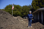 In this Wednesday, April 11, 2018, photo, mudslide survivor Mari Mitchel pauses for photos next to a pile of dirt outside her home that was devastated by the mudslide, in Montecito, Calif. The mudslide carried away everything from massive pieces of antique family furniture to a tiny pouch filled with her most treasured jewelry, including her wedding and engagement rings. But a week earlier, Mitchel got what she calls her