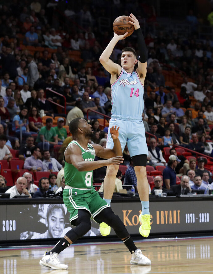 Miami Heat guard Tyler Herro (14) attempts a 3-pointer as Boston Celtics guard Kemba Walker (8) defends during the first half of an NBA basketball game, Tuesday, Jan. 28, 2020, in Miami. (AP Photo/Lynne Sladky)
