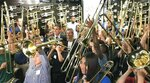 Fifty students surround Max Schachter and Fred Schiff to blast a B-flat on their new Alex Tribute Trombones Saturday, May 11, 2019 at All County Music in Tamarac, Fla. Fifty special trombones have been given out to band students throughout Florida in honor of 14-year-old Alex Schachter, who was a trombone player in the marching band at Marjory Stoneman Douglas High School and who died in the Parkland high school shooting. (Wayne K. Roustan/South Florida Sun-Sentinel via AP)