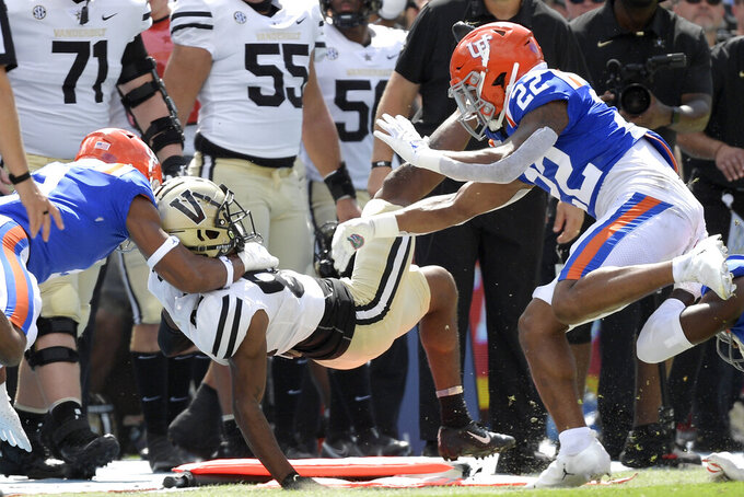 Vanderbilt wide receiver Devin Boddie Jr. (82) is tackled out of bounds by Florida linebacker Mohamoud Diabate, left, and safety Rashad Torrence II (22) on a running play in the first half of an NCAA college football game, Saturday, Oct. 9, 2021, in Gainesville, Fla. Diabate was penalized on the play. (AP Photo/Phelan M. Ebenhack)