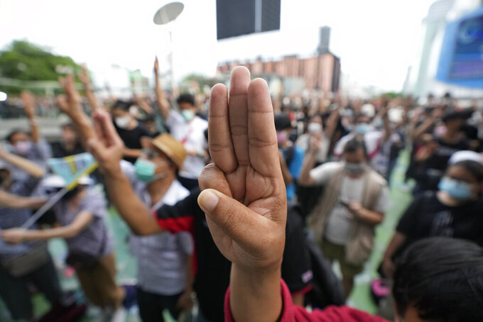 Pro-democracy supporters display the three-finger symbol of resistance during a demonstration in Bangkok, Thailand, Thursday, June 24, 2021. Pro-democracy protesters have taken to the streets of Thailand's capital, marking the 89th anniversary of the overthrow of the country's absolute monarchy by renewing their demands that the government step down, the constitution be amended and the monarchy become more accountable. (AP Photo/Sakchai Lalit)