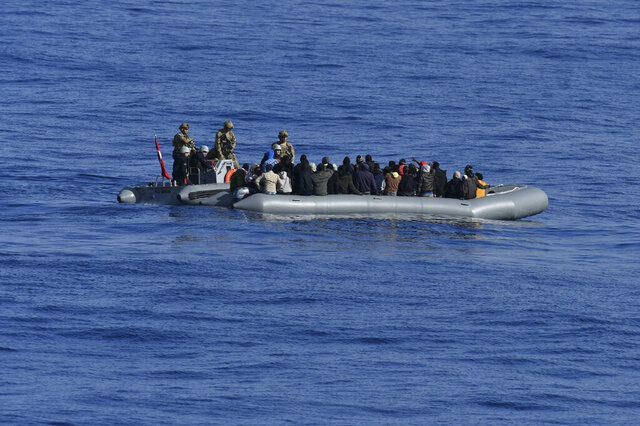 In this image provided by the Turkish Military, members of Turkish forces, left, approach migrants aboard a dinghy in the mid Mediterranean Sea, Wednesday, Jan. 29, 2020.  The military said that a military ship, TCG Gaziantep, assisted the migrants and provided medical aid before handing them over to the Libyan Coast Guard. The frigate is in the region to support NATO's Mediterranean Shield Operation and to assist NATO's Marine Guard Operation. (Turkish Military via AP)