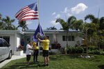 The Hixon family, sons of Chris Hixon, Corey, left, and Tom, right, lower the flag to half staff on the second anniversary of his death on Friday, Feb. 14, 2020, in Hollywood, Fla. Hixon was killed in a school shooting on Valentine's Day two years ago at Marjory Stoneman Douglas High School. His widow Debbi recently had the family home renovated by the program