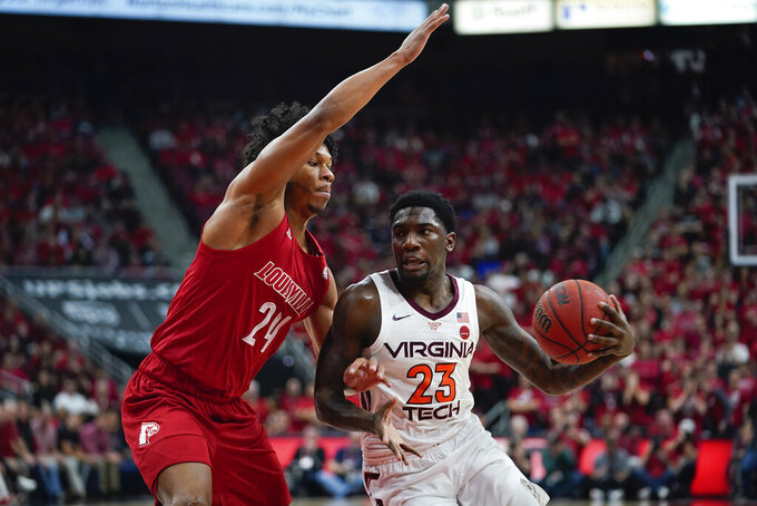 Virginia Tech guard Tyrece Radford (23) drives toward the basket around Louisville forward Dwayne Sutton (24) during the first half of an NCAA college basketball game, Sunday, March 1, 2020, in Louisville, Ky. (AP Photo/Bryan Woolston)