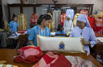 In this Friday, Nov. 8, 2019, photo, Sister Sukanya Sukchai, right, inspects a newly made pillow at a Catholic preparatory school in Bangkok, Thailand. Seamstresses from the Congregation of the Sacred Heart of Jesus Sisters of Bangkok are studiously snipping and sewing. They've been working tirelessly, running up the ceremonial garments Pope Francis will wear during his four-day visit to Thailand later this month. (AP Photo/Gemunu Amarasinghe)