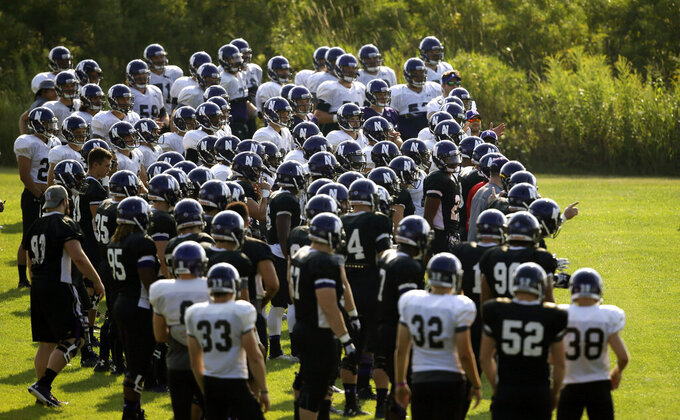 """FILE - Northwestern football players gather during practice at the University of Wisconsin-Parkside campus in Kenosha, Wisc., in this Monday, Aug. 17, 2015, file photo. College football players and some other athletes in revenue-generating sports are employees of their schools, the National Labor Relations Board's top lawyer said in a memo Wednesday, Sept. 29, 2021, that would allow the players to unionize and otherwise negotiate over their working conditions. The nine-page NLRB memo revisited a case involving Northwestern University football players who were thwarted from forming a union when the board said that taking their side """"would not promote stability in labor relations.""""(AP Photo/Jeffrey Phelps, File)"""