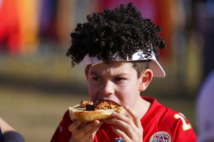 A Kansas City Chiefs fan eats a sandwich before the NFL Super Bowl 55 football game between the Kansas City Chiefs and Tampa Bay Buccaneers, Sunday, Feb. 7, 2021, in Tampa, Fla. (AP Photo/Mark Humphrey)